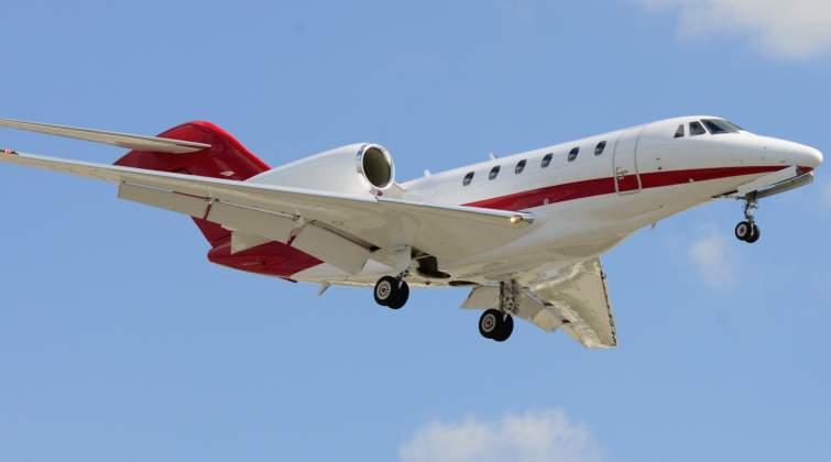 This beautiful red and white Citation X is captured on camera during a landing as it descended to th