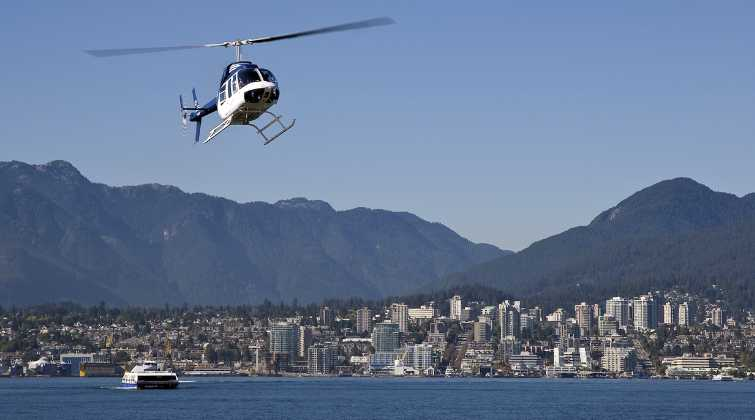 Heli jet helicopter on a charter flight in Burrard Inlet near downtown Vancouver, BC, Canada. Kelown